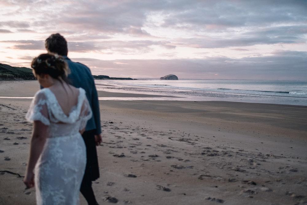 Couple walking on beach at Ravensheugh Log Cabin.