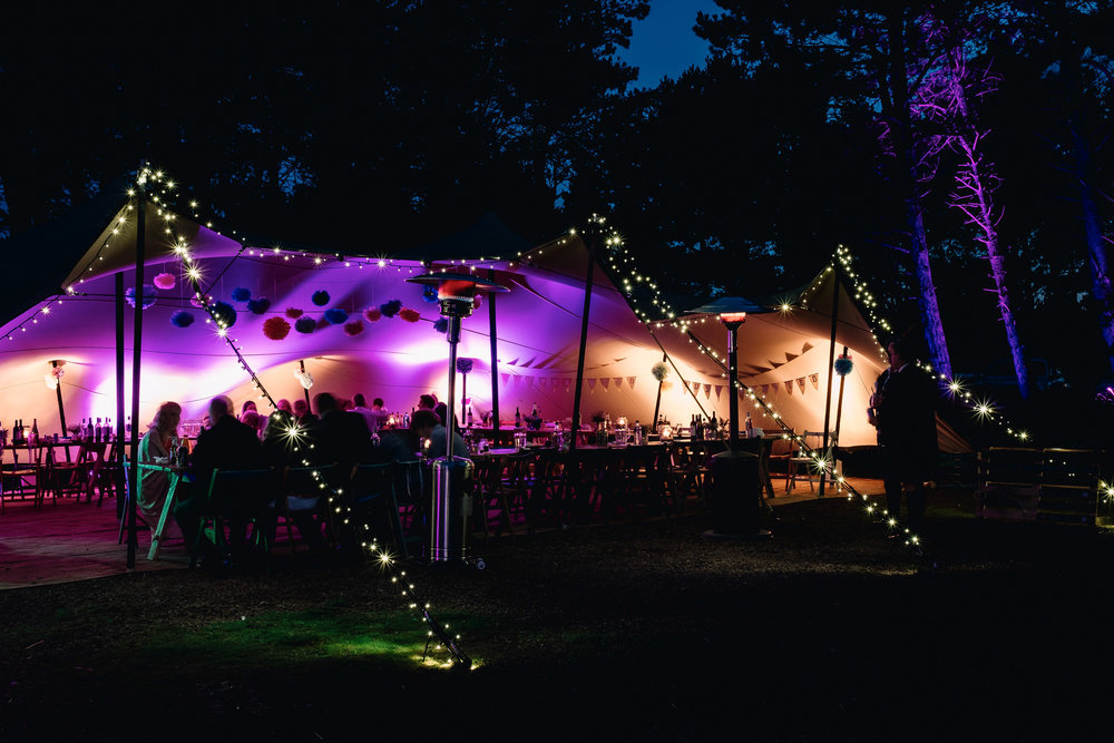Tent lit up for the wedding party at night.