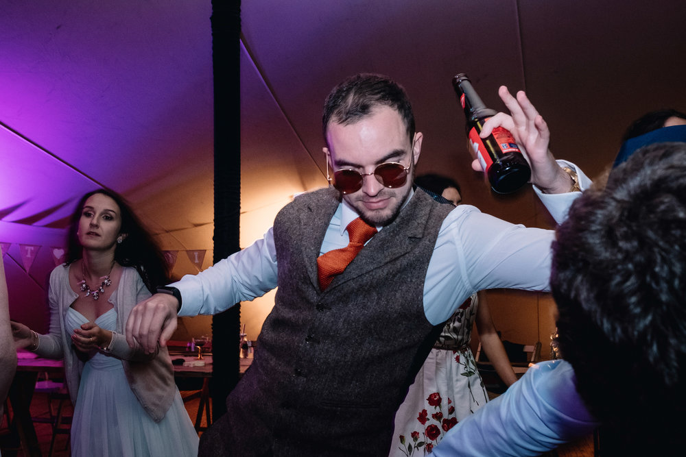 Male dances enthusiastically wearing round shades.