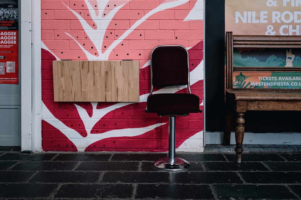A red velvet chair stands to the left of a wooden bench.