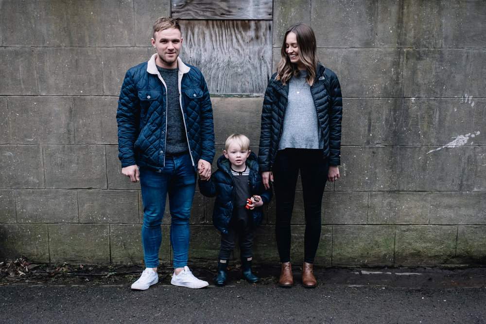 Parents stand on either side of their son and hold his hand.