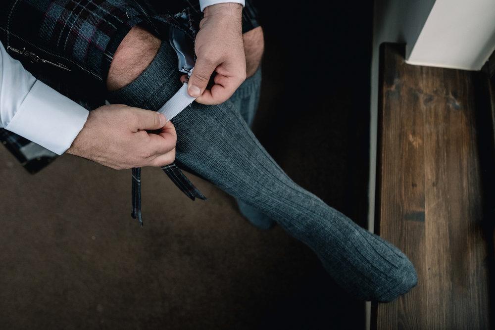 Groom fixing his socks.