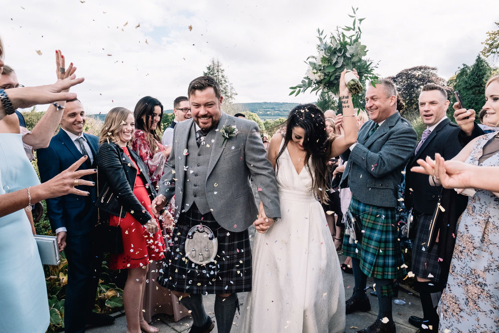 Guests throw confetti at bride and groom.