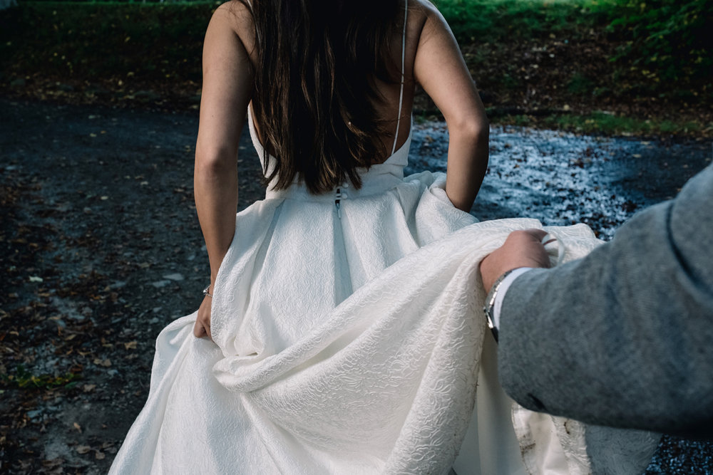Groom holds bride's dress as they walk outside.