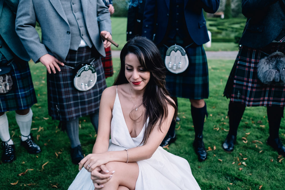 Bride sitting down whilst surrounded by smoking guests.