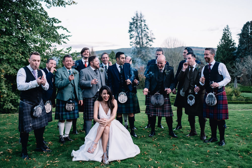 Bride sits and laughs - she is surrounded by the groom and the groomsmen who are smoking cigars.