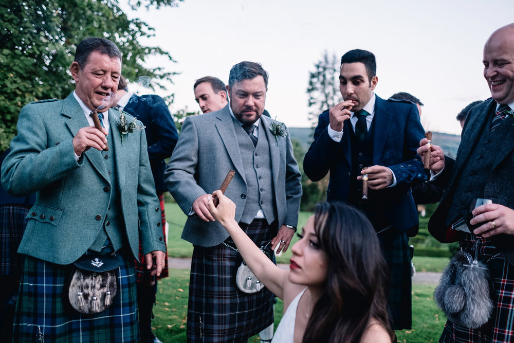 Groom takes bride's cigar from her.