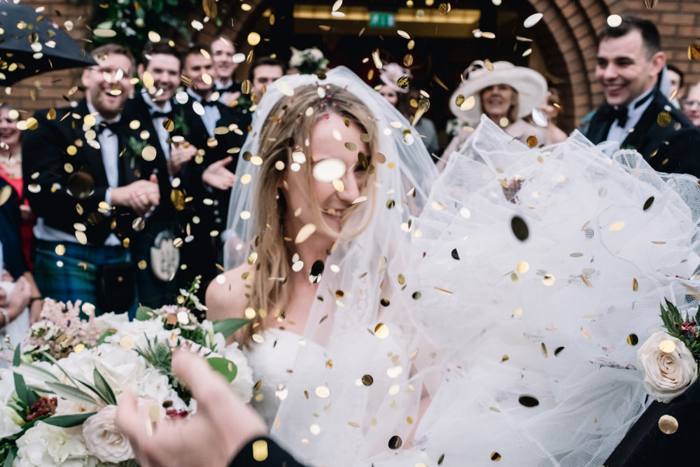 A bride is surrounded by gold confetti.