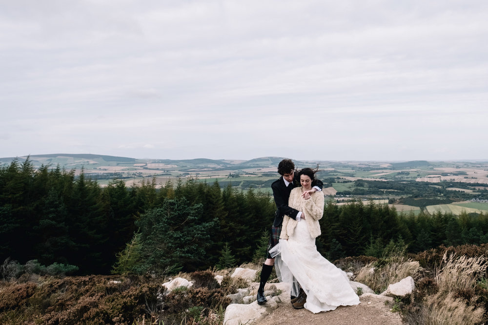 Bride and groom stand on Bennachie.