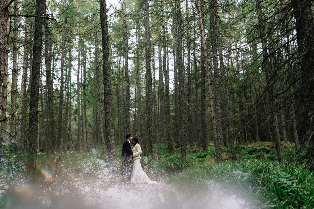 Bride and groom stand in a woodland area, embracing each other.