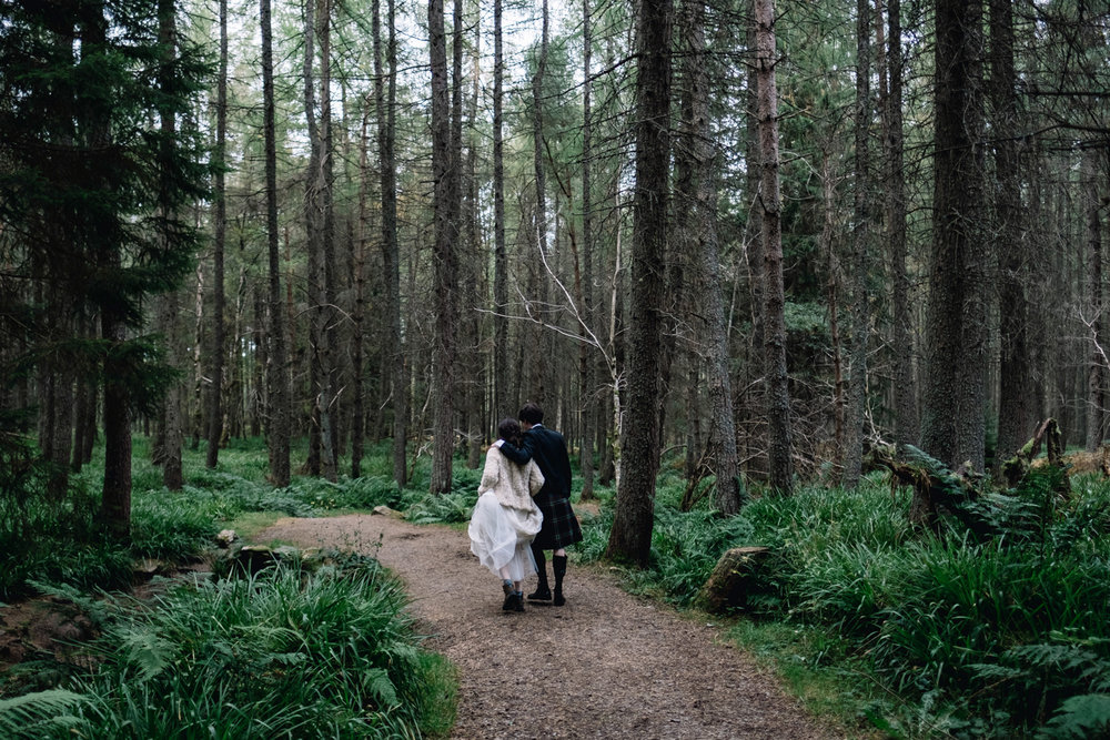 Couple walking in a woodland area.