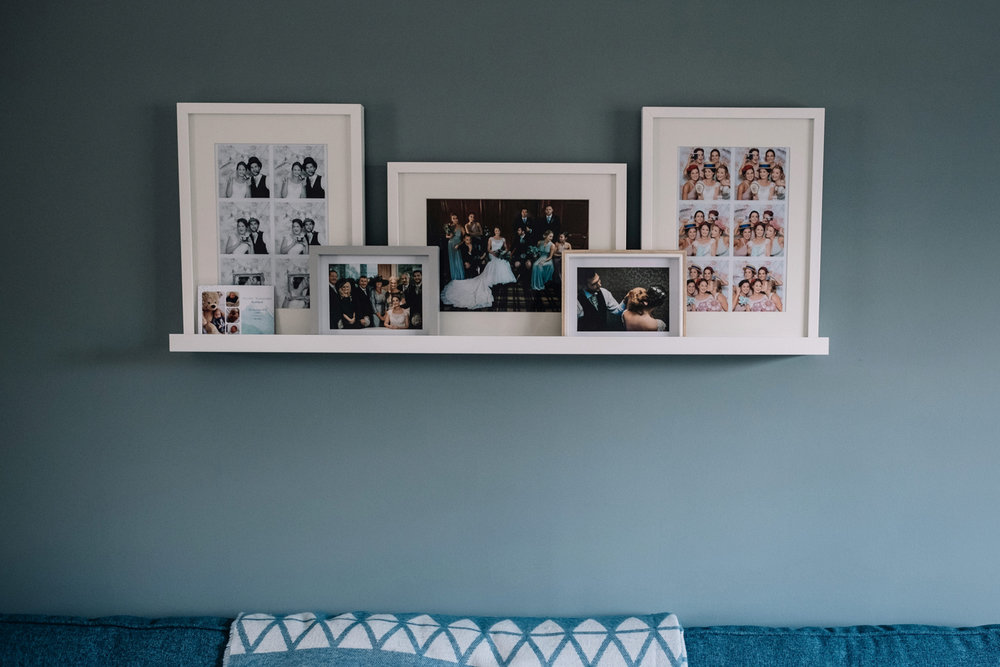 Living room wall featuring wedding photos of the couple's house.