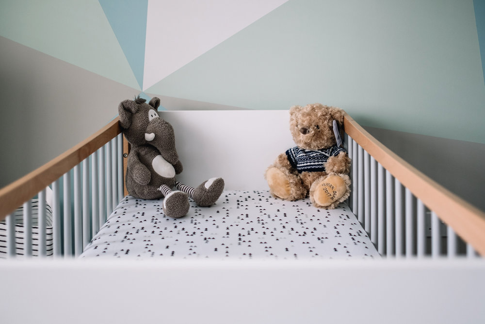 Two teddies are at the top of a baby's cot.