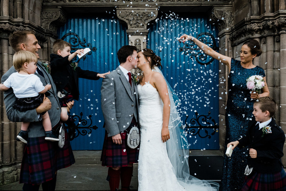 A couple face each other and kiss against a backdrop of two blue doors whilst their closest of kin throw confetti over them.