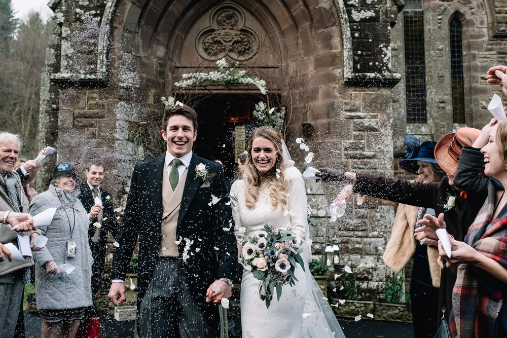 A smiling couple leave the church at Drumtochty Castle and are being covered in lavender.