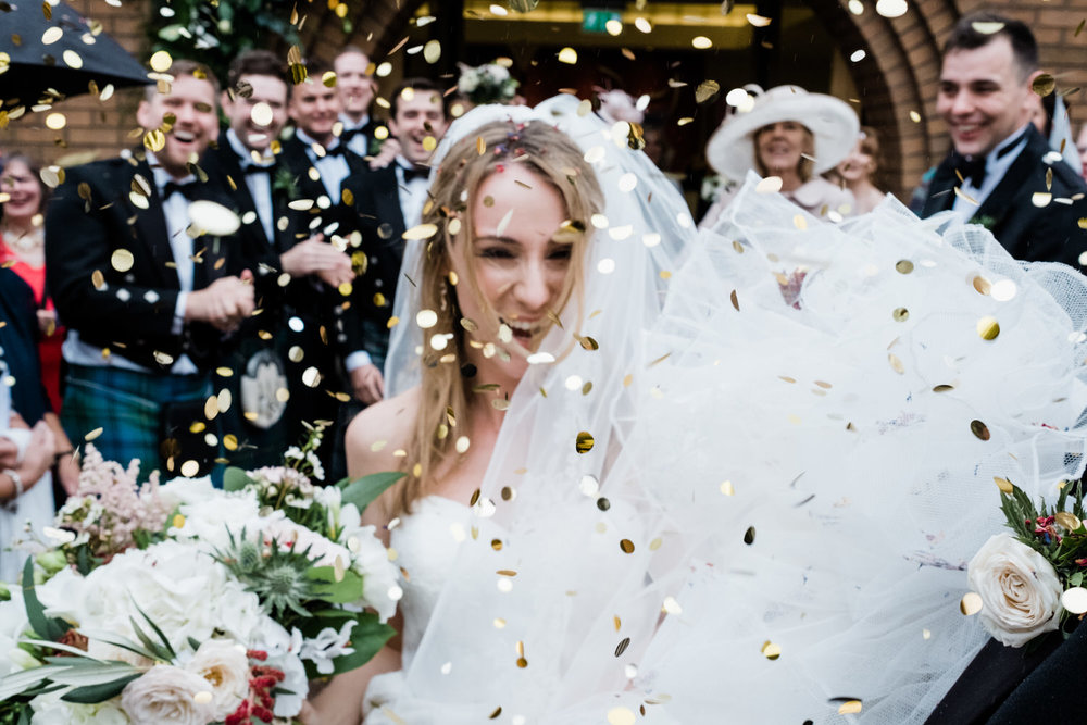 A close up and out of focus photograph of a bride covered with confetti.