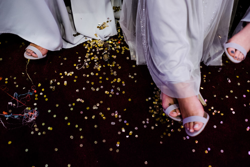 Gold confetti litters the red carpet and contrasts with the bridesmaids violet coloured shoes and dresses.