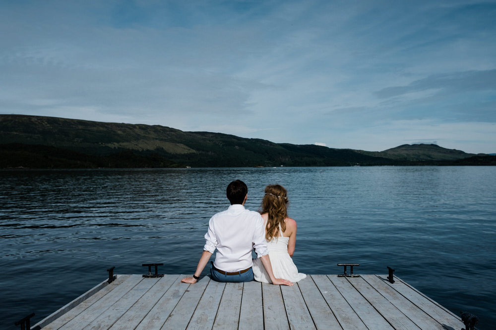 couple sit on a pier in Loch Lomond