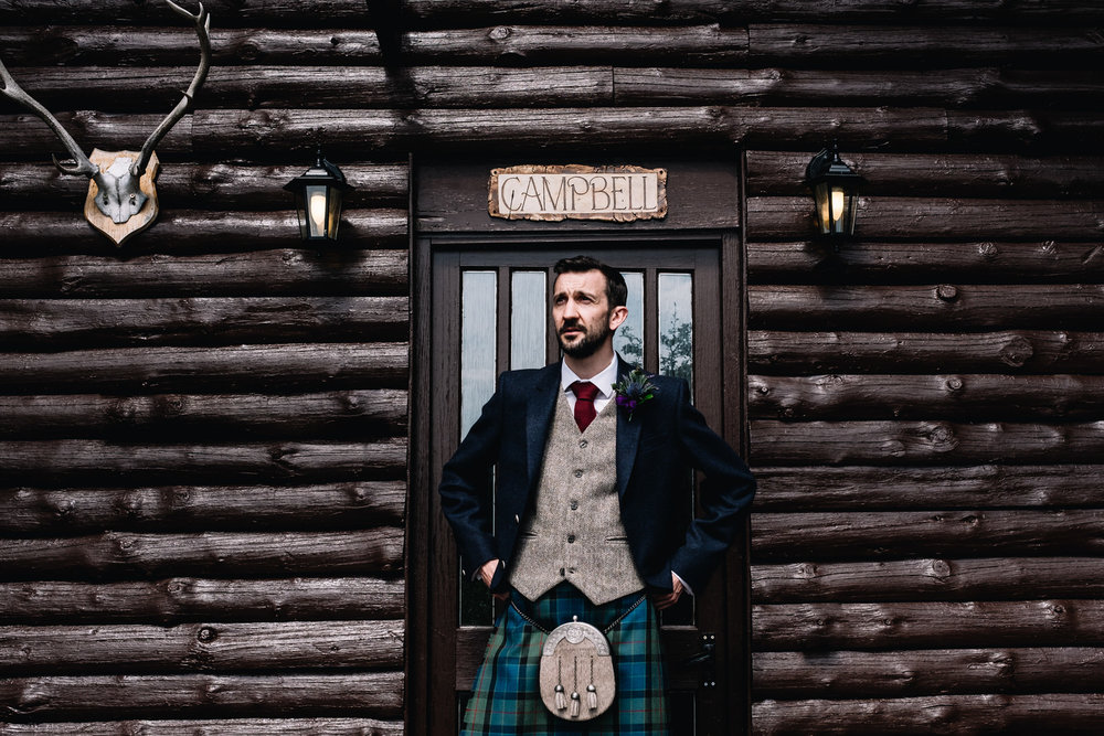 A groom stands at the front of his cabin on Lennie Estate