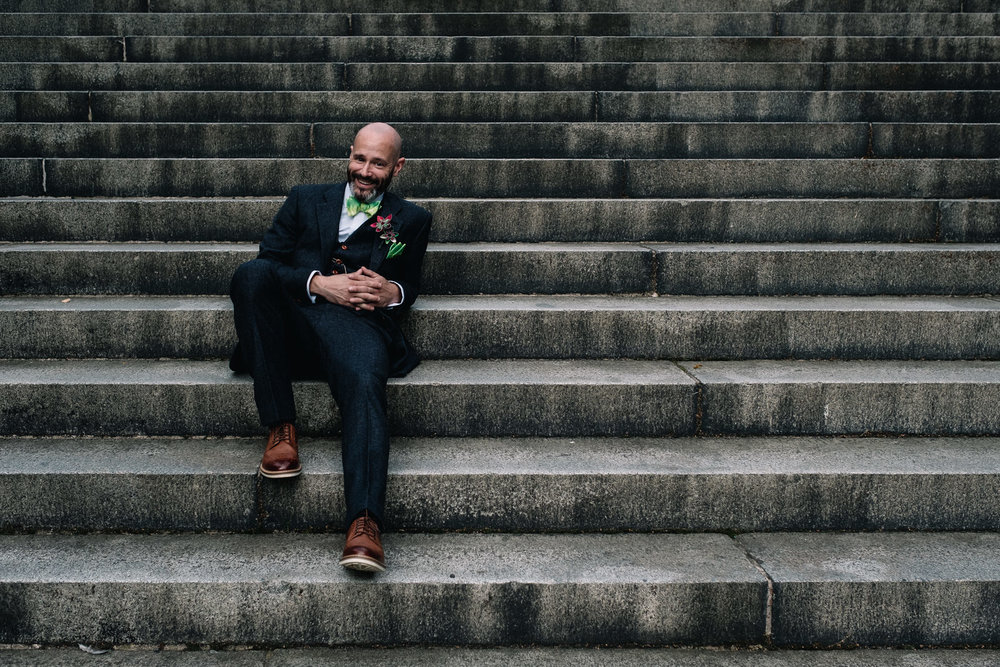 A groom sits on the stairs leading up to Park Circus in Glasgow's West End.