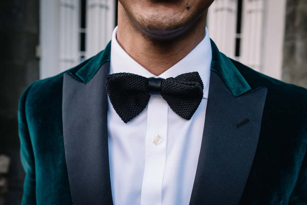 A groom is wearing a racing green velvet dinner jacket and a black bow tie.