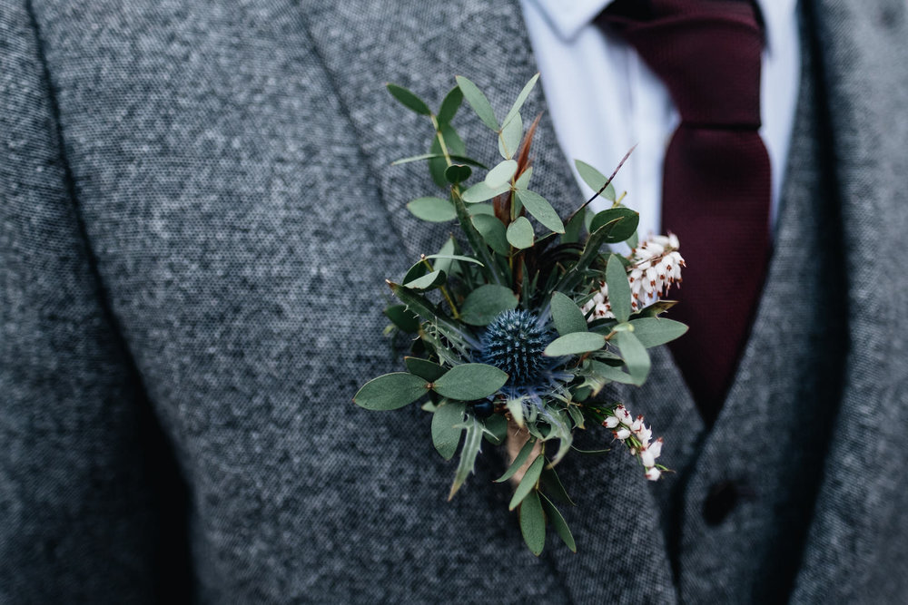 A groom is wearing a thistle buttonhole