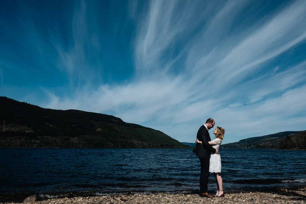 Loch tay elopement and a couple embrace on the beach.