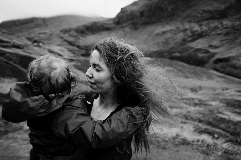 mother's hair is being swept away by wind as she holds her child