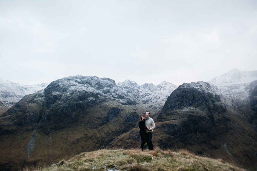 couples standing with snow capped mountains behind in Glencoe