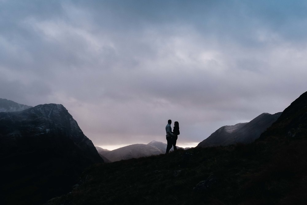 Couple embrace high up in mountains