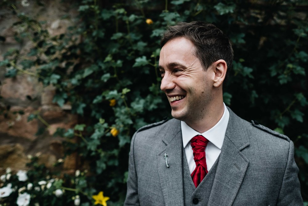 similing groom portrait against green foliage backdrop