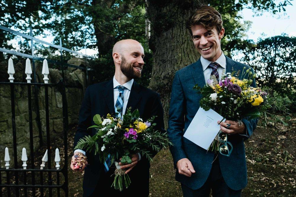 two men holding bright bridal boquets
