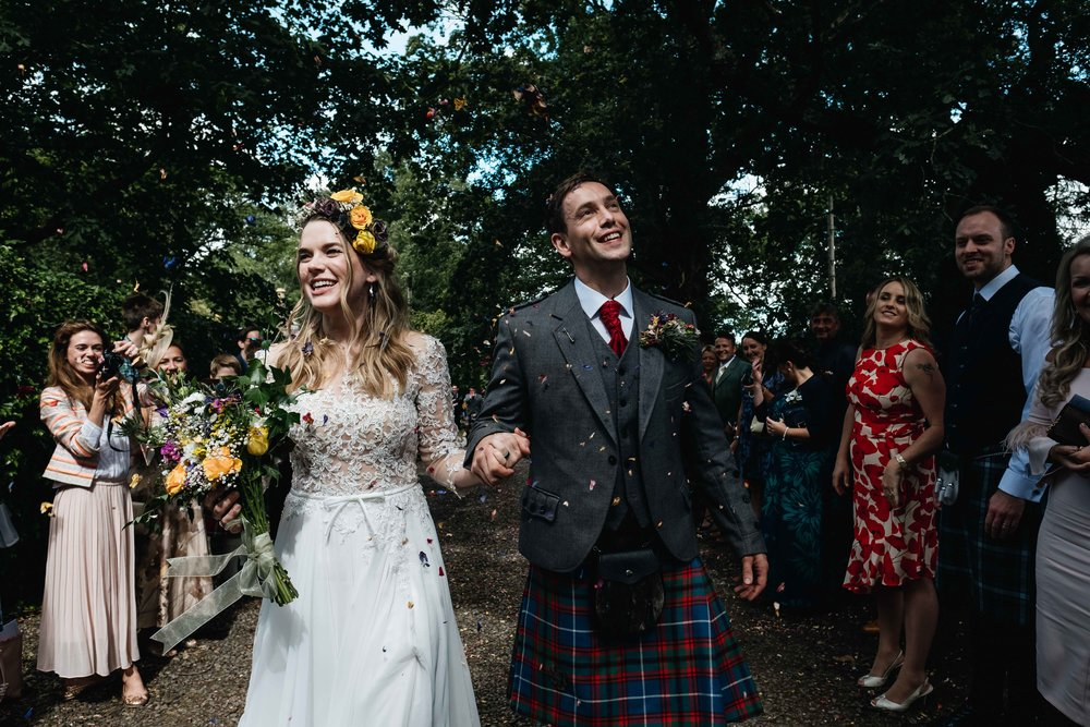 bride and groom smiling after guests have thrown confetti at them