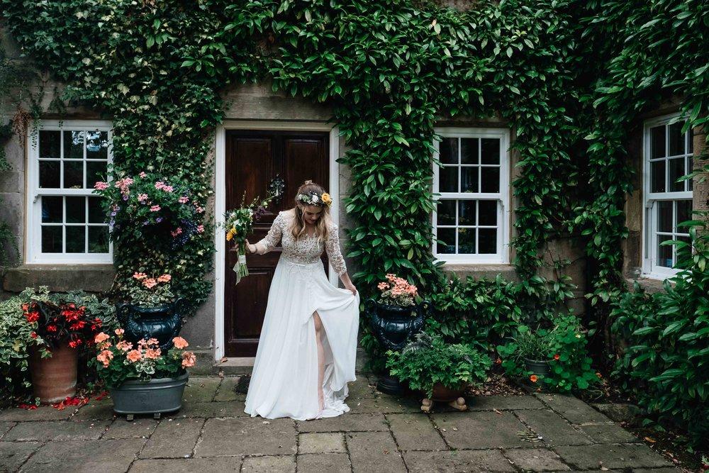 a full length shot of the bride adjusting her dress