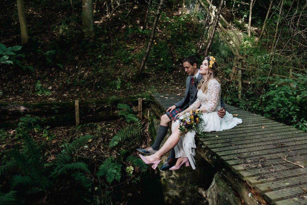 bride and groom sitting on a bridge on the groom's estate