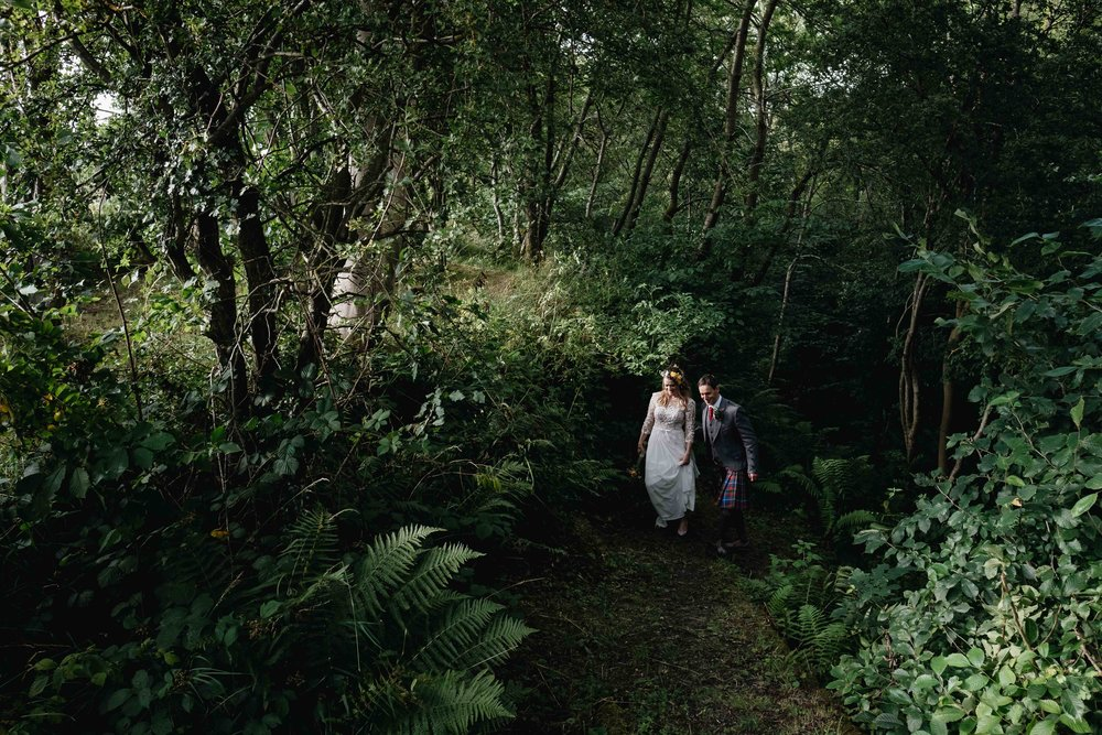 bride and groom walking in a forrest lit by a shard of sunlight shining through