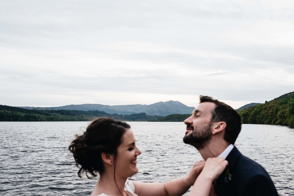 bride fixes groom's tie for him but the hill in the background is what's in focus
