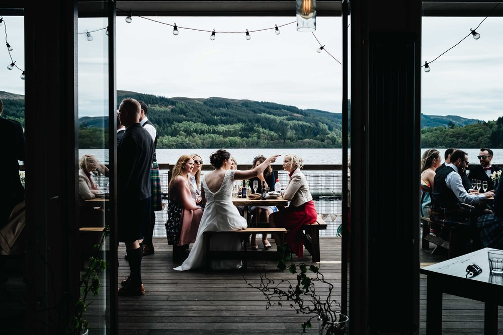 guests and bride sit outside by loch enjoying the wedding drinks' reception
