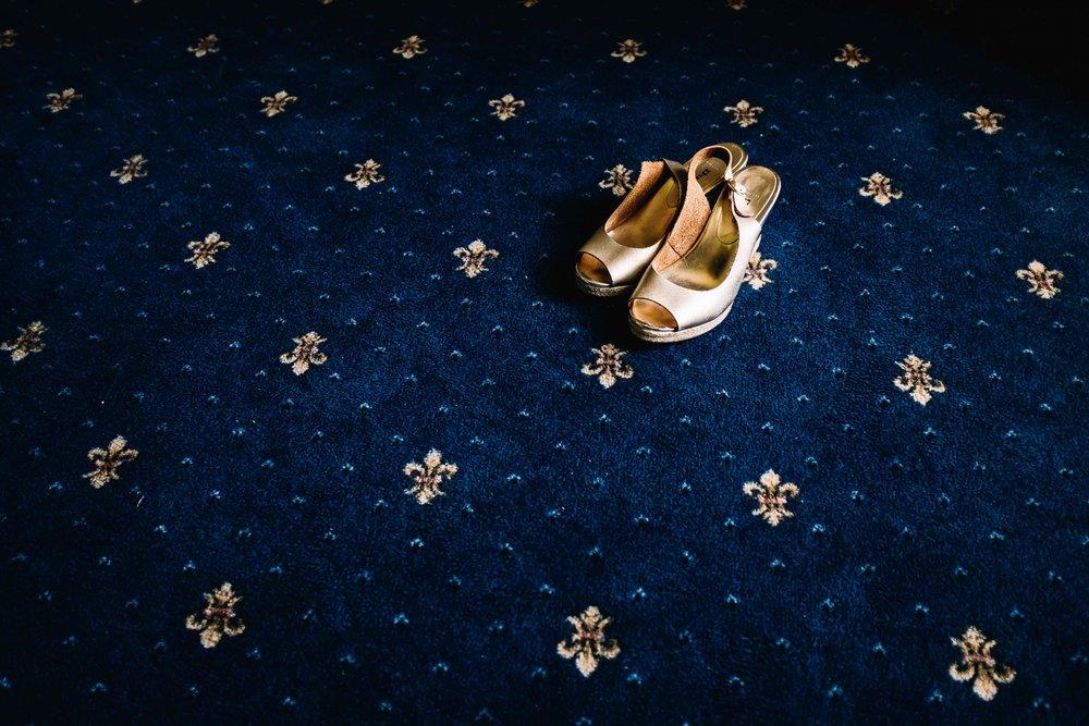 gold bridal shoes against blue carpet