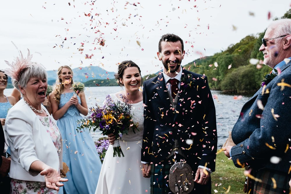 couple laughing while confetti being thrown at them