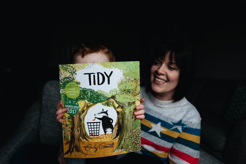 young boy holds his book 'Tidy' up to the camera