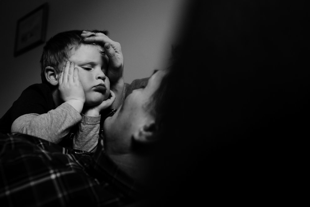 father holds his son close and holds back his hair