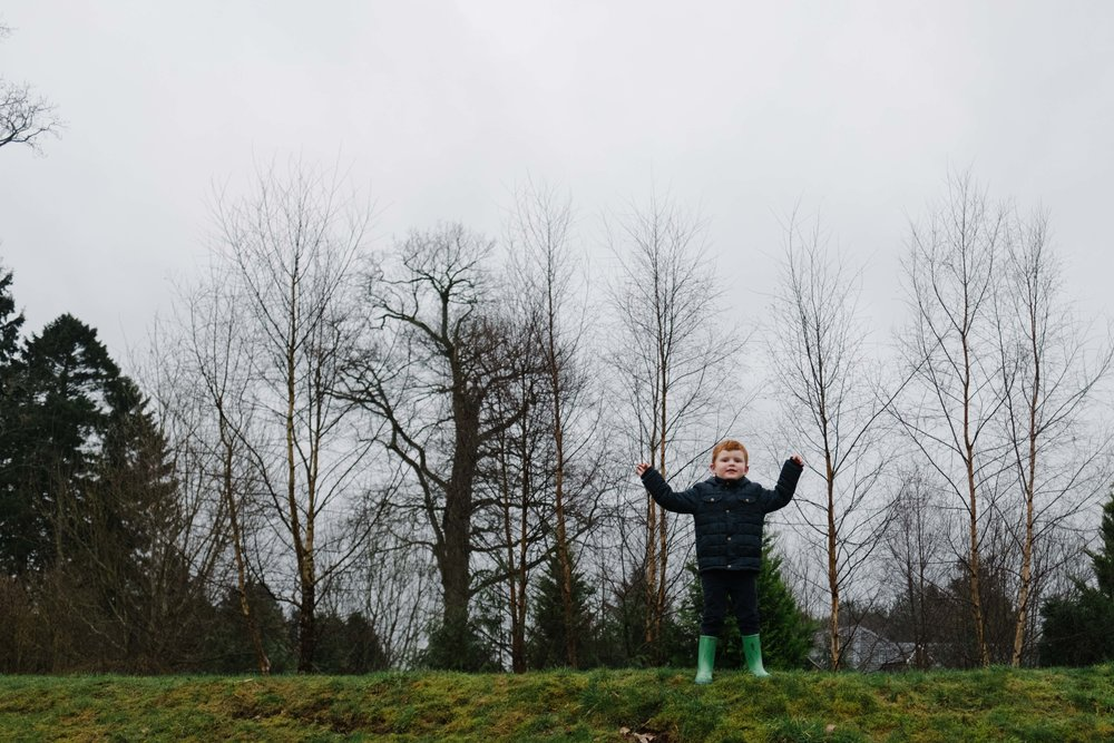 boys standing on hill holding his hands up high