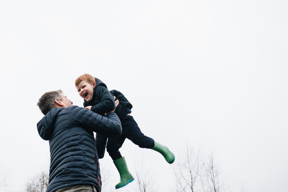 father holding his son up high