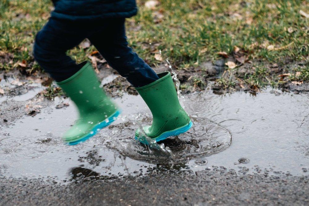 boy wearing green wellies runs through a puddle