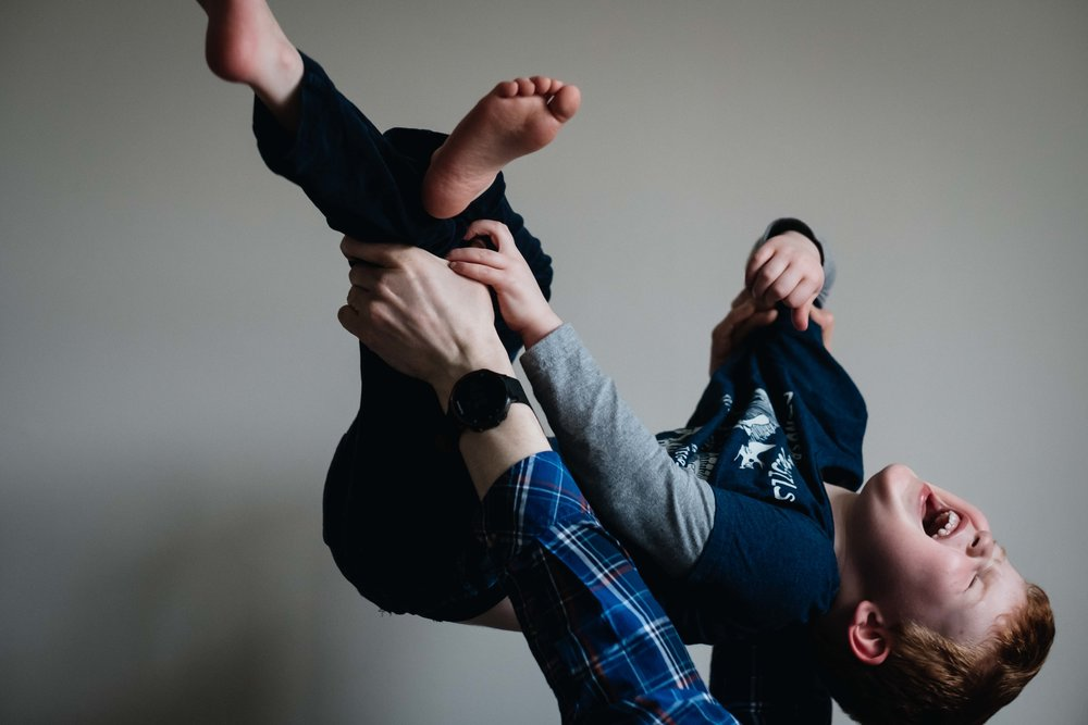 father holding his son aloft with his hands and son is laughing