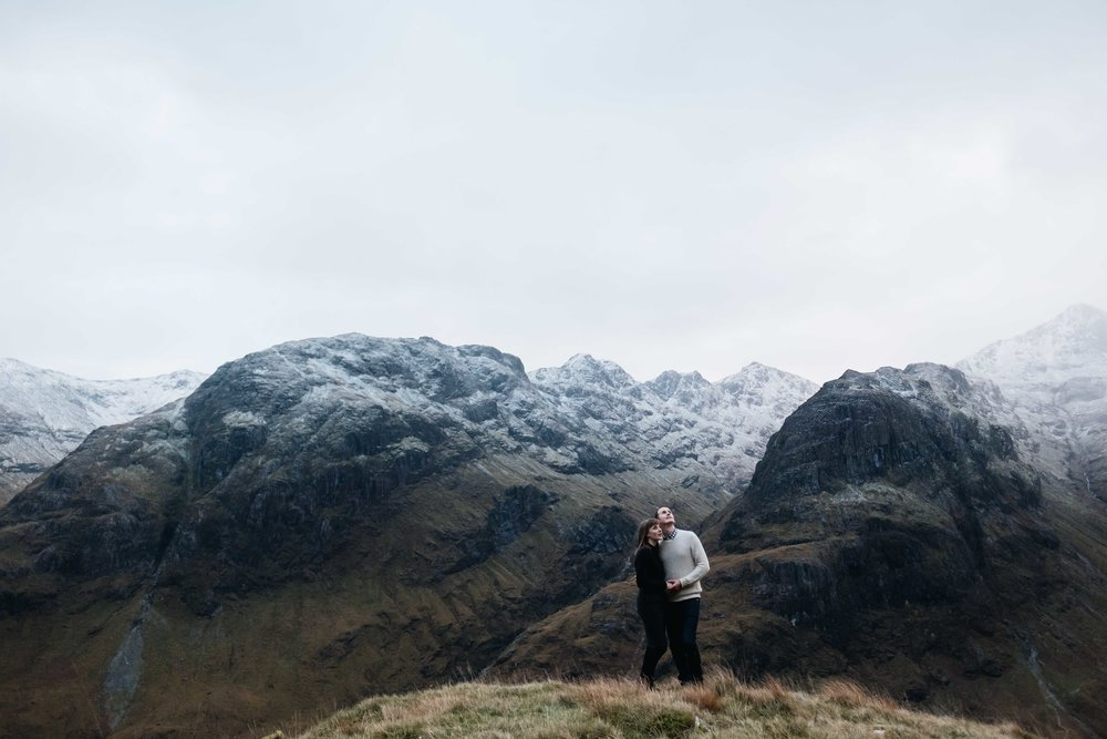 a wide angled persecptive of a couple embracing and looking at the sky in Glencoe with snow capped mountains behind