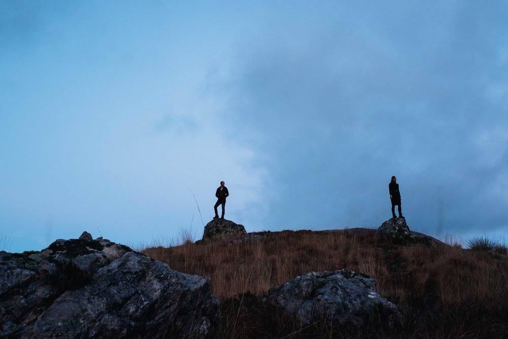 A couple standing separately on a rock