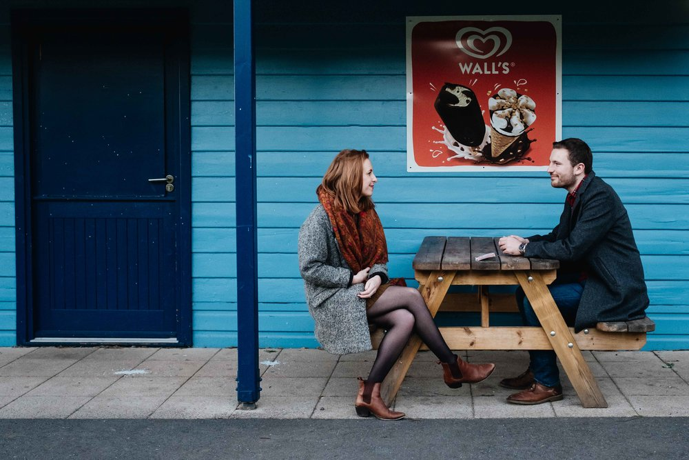 a couple are sitting looking at each other outside an ice cream shop