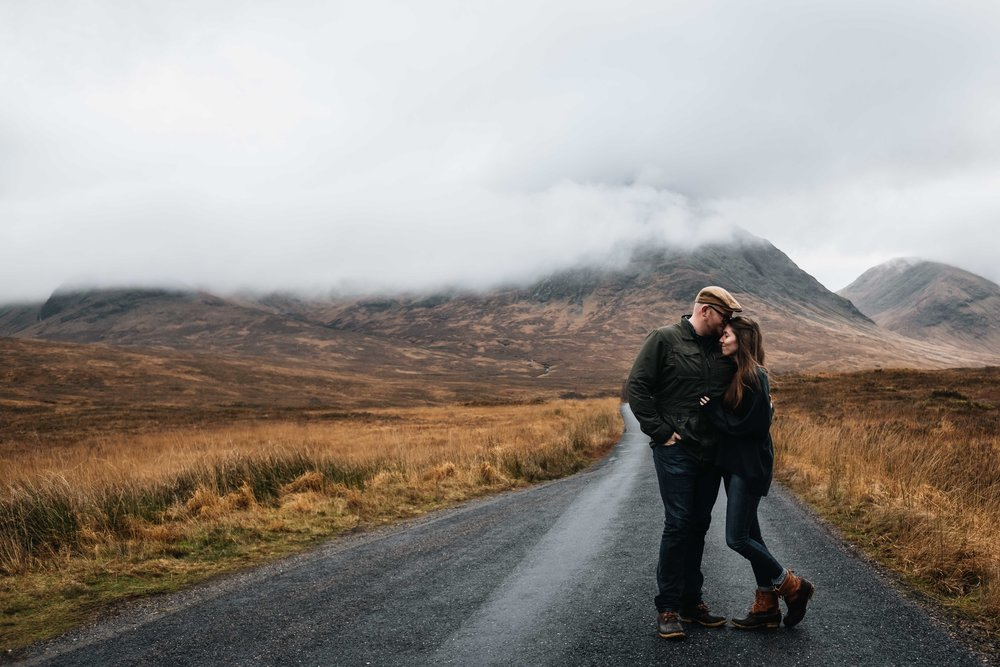 A couple stand on a road with mountains behind them and they are in a loving embrace.